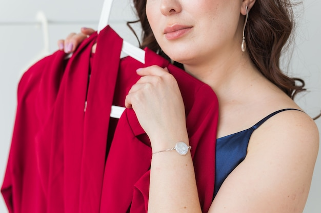 Mooi meisje jurk kijken tijdens het kiezen van een geschikte. mode-, verkoop- en winkelconcept.