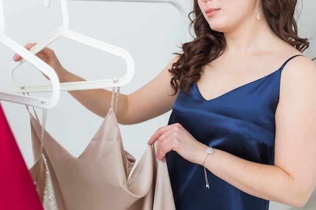 Mooi meisje jurk kijken tijdens het kiezen van een geschikte