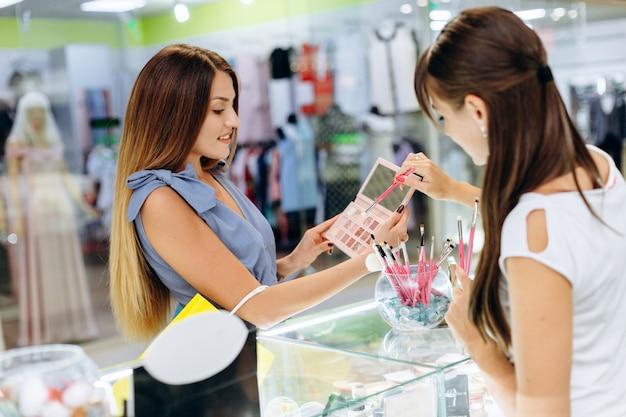 Mooi meisje kiest cosmetica in het winkelcentrum.