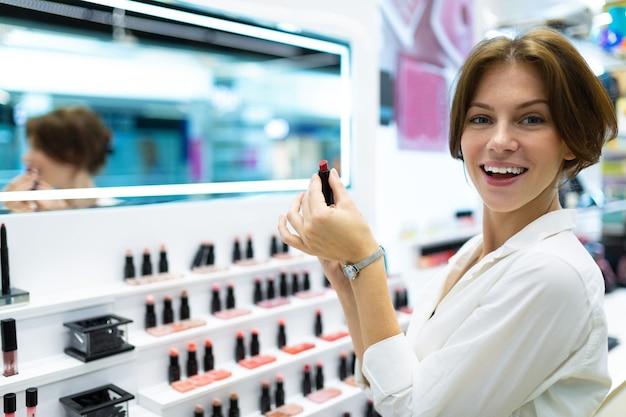 Mooi meisje kiest een lippenstift in de winkel en denkt