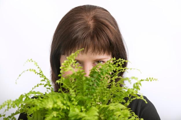 Mooi meisje kijkt uit van achter een bloem. jonge vrouw verstopte zich achter een ingemaakte binnenbloem. portret van een bloemist