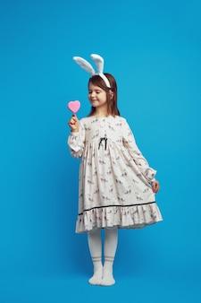 Mooi meisje koekje in de hand in vorm van hart over blauwe muur te houden