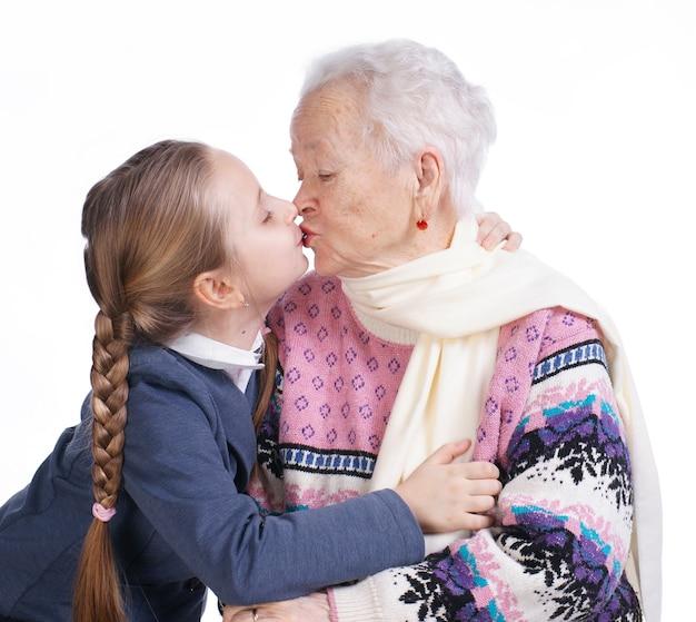 Mooi meisje kuste haar grootmoeder op een witte achtergrond