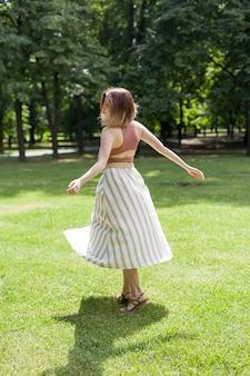 Mooi meisje lacht en danst buiten in een weiland tijdens zonsondergang.