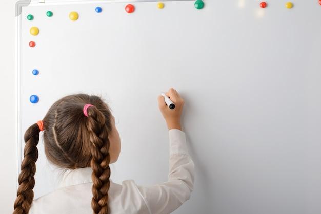 Mooi meisje leerling van de middelbare school schrijven op het bord