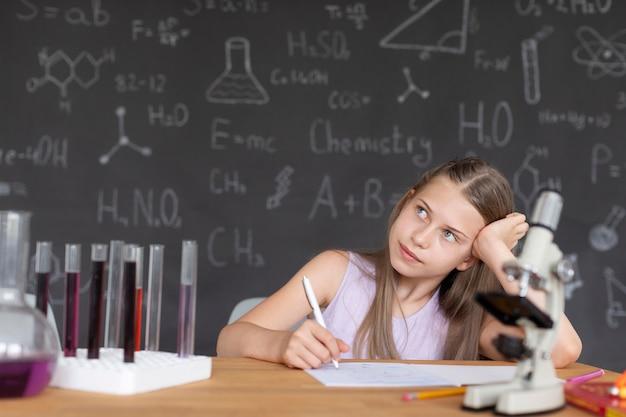 Mooi meisje leert meer over scheikunde in de klas