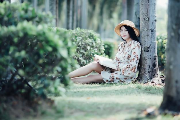Mooi meisje leesboek in het park in de zomerzon licht