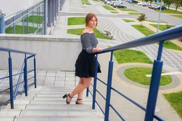 Mooi meisje leunde op de reling terwijl ze de trap van een modern kantoorgebouw afliep