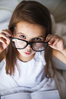 Mooi meisje lezen van een boek in bed met bril, onderwijs, interesses, toekomstige student
