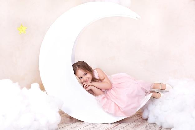 Mooi meisje ligt in studio met decor van maan, sterren en wolken. kind droomt. schattig meisje zit op een decoratieve maan met katoen wolken en sterren. gezond slaapconcept. kindertijd