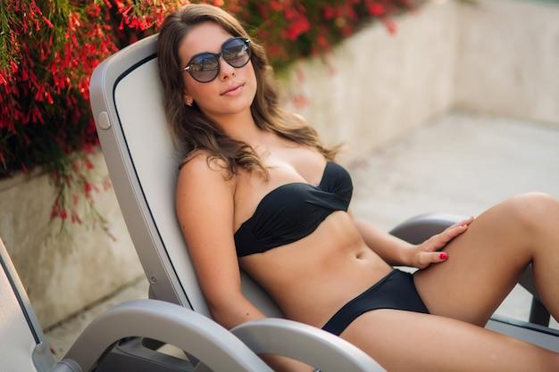 Mooi meisje ligt op de ligstoel. zonnige zomerdag