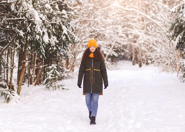 Mooi meisje loopt door de sneeuw in de winter in het park