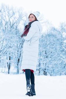 Mooi meisje loopt door het besneeuwde bos met een boek in haar handen