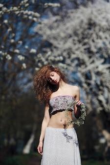 Mooi meisje loopt in de weelderige tuin gekleed in een krans