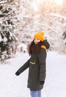 Mooi meisje loopt in het bos van de winter op een zonnige dag