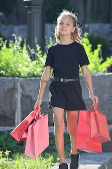 Mooi meisje loopt in het park met gekleurde tassen