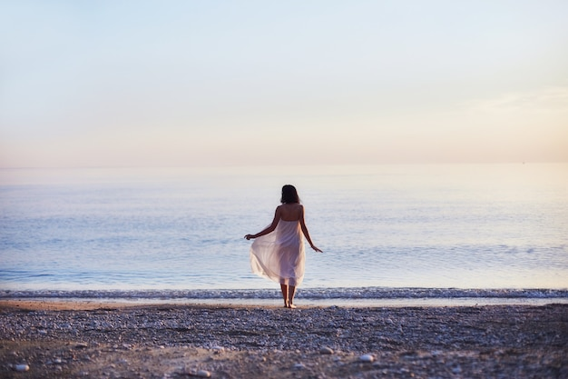Mooi meisje loopt langs het strand op een zonnige dag. slanke sexy vrouw die op de zee rust
