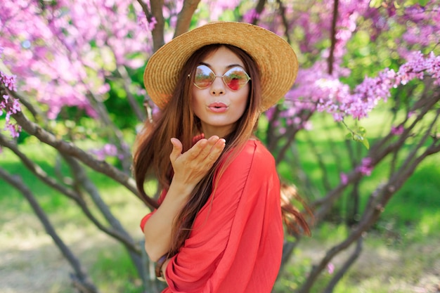 Mooi meisje lucht kus verzenden naar camera in zonnige lentedag. roze bloeiende bomen o