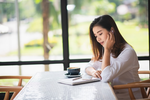 Mooi meisje luisteren muziek in het café en drinken wat koffie