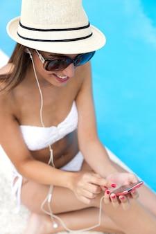 Mooi meisje luisteren naar muziek in het zwembad.