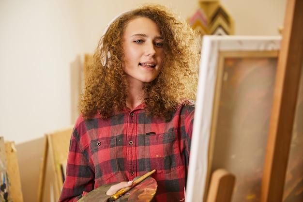 Mooi meisje luistert naar muziek via een koptelefoon en zingt tijdens het tekenen van een schilderij