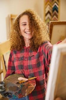 Mooi meisje luistert naar muziek via een koptelefoon, lacht en tekent een schilderij