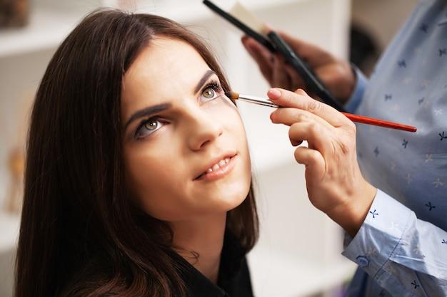 Mooi meisje maakt gebruik van de diensten van een professionele visagist in een schoonheidssalon
