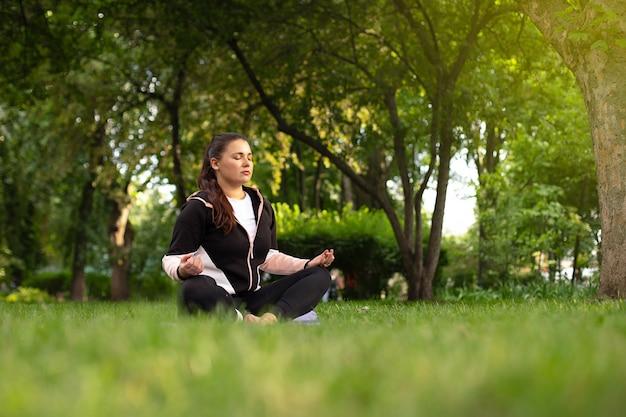 Mooi meisje mediteert in de lotuspositie op het groene gras omringd door bomen