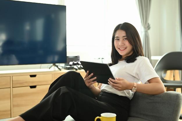 Mooi meisje met behulp van digitale tablet en lachend zittend op de bank thuis.