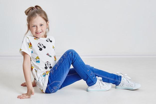 Mooi meisje met blauwe ogen die op vloer en het glimlachen zitten. blondemeisje met sproeten op haar gezicht