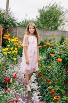 Mooi meisje met blauwe ogen en lang blond haar. klein meisje in een roze flamingo jurk. meisje in de bloementuin. zomer heldere, emotionele foto. grote, dikke, lichte bloementuin bij het huis.