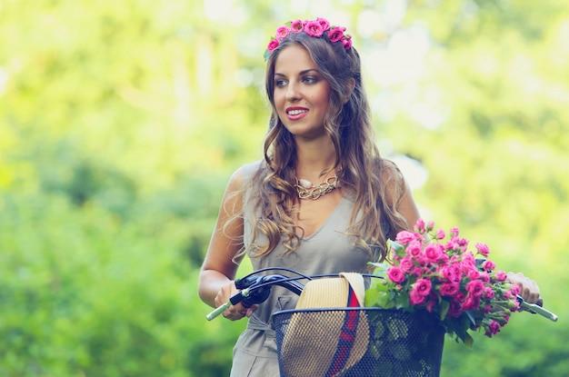 Mooi meisje met bloemen op een fiets