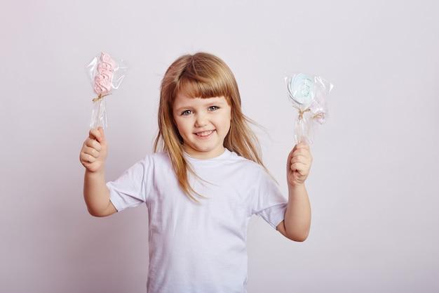 Mooi meisje met blond haar eet een lolly, ronde karamel op stok in handen van vrolijk lachend meisje. babymeisje met lang haar in wit t-shirt likt lollipop. rusland, sverdlovsk, 1 december 2018