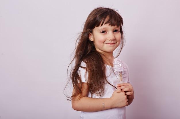 Mooi meisje met blond haar eet een lolly, ronde karamel op stok in handen van vrolijk lachend meisje.