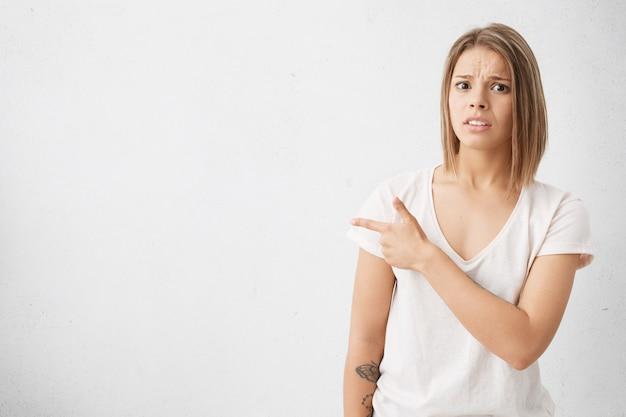 Mooi meisje met bob-kapsel dat bang of geschokt gelaatsuitdrukking heeft, haar wijsvinger zijwaarts richt op witte lege muur met copyspace