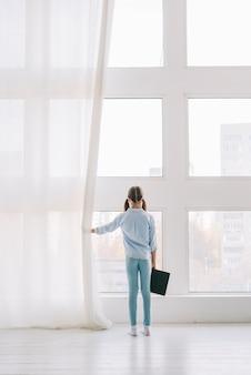 Mooi meisje met boek kijkt door het raam