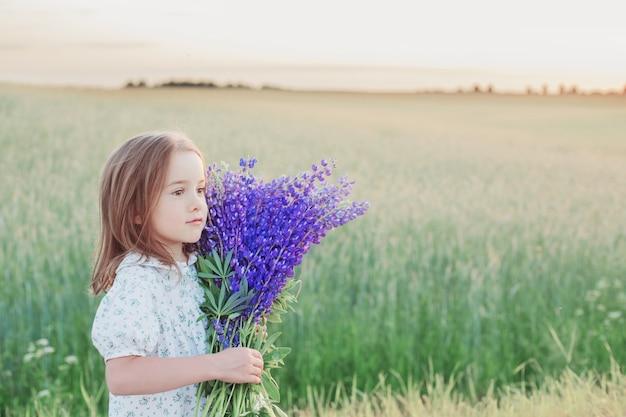 Mooi meisje met boeket bloemen bij zonsondergang