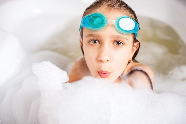 Mooi meisje met bril baadt in een badkuip genieten van zomervakantie thuis tijdens het coronavirus.