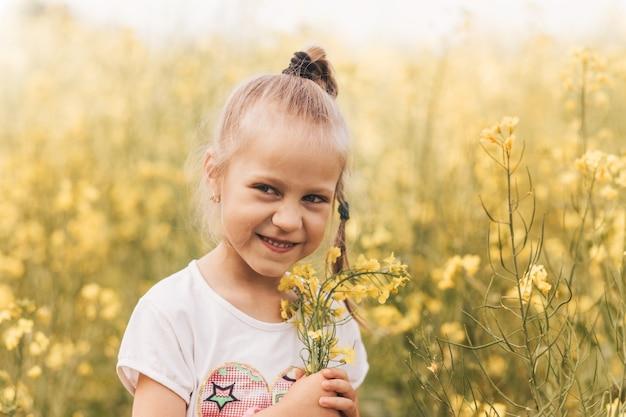 Mooi meisje met canola bloemen op het veld in de zomer. zomer vakantie seizoen. zorgeloze levensstijl in de kindertijd. geluk.