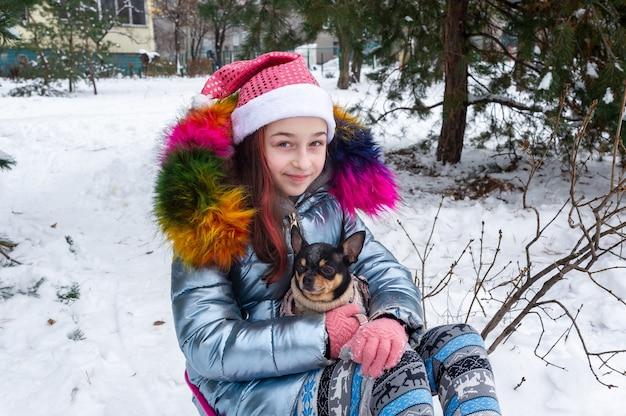 Mooi meisje met chihuahua over de aard. een tiener die de sneeuwwinter van een hondchihuahua houdt