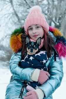 Mooi meisje met chihuahua over de aard. tiener meisje en chihuahua in de winter op straat.