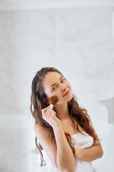 Mooi meisje met cosmetische poederborstel voor make-up. bedenken. make-up aanbrengen voor een perfecte huid.
