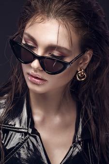 Mooi meisje met creatieve kunst make-up, zwarte jurk en gouden accessoires. mooi gezicht.