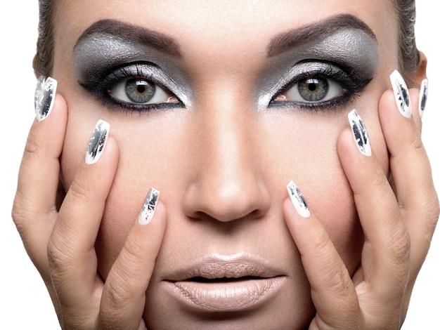 Mooi meisje met de zilveren make-up en metaalspijkers.