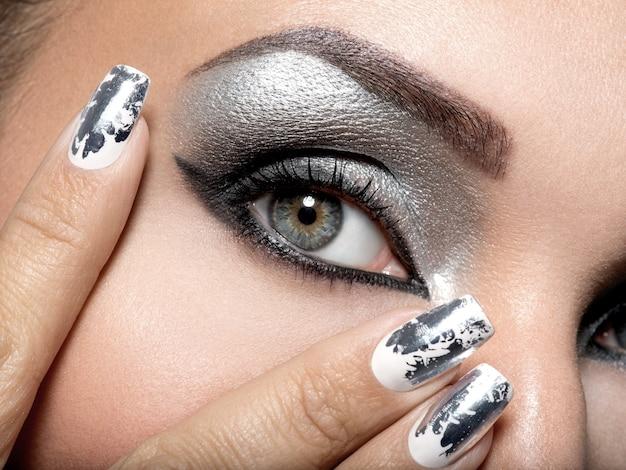 Mooi meisje met de zilveren make-up van ogen en metalen nagels.