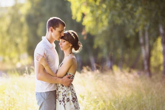 Mooi meisje met donker haar en bruine ogen met een krans op hoofd in zomerjurk knuffelen een man in een wit overhemd op een groene achtergrond. verliefde paar in het bos op een zonnige dag. van elkaar houden