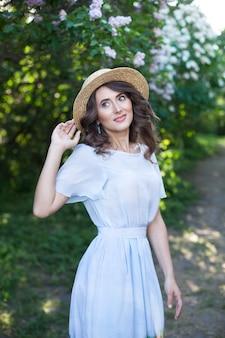 Mooi meisje met donker haar in een strohoed op een achtergrond van vrouwelijkheid in de zomertuin vintage
