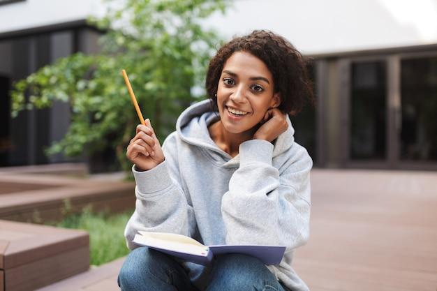 Mooi meisje met donker krullend haar, zittend met open boek op knieën en gelukkig