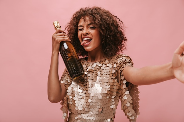 Mooi meisje met donkerbruin golvend haar in glanzende jurk die knipoogt met tong, fles met drankje vasthoudt en foto maakt op roze muur..