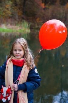 Mooi meisje met een ballon. portret van een blond meisje met bruine ogen met een ballon op de achtergrond van de herfst. fotoshoot